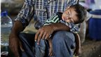 Boy sleeping on his father's arm at the Bab Al-Salameh crossing
