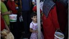 Syrian girl queuing for bread at the Bab Al-Salameh crossing