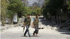 Two Free Syrian Army fighters walking in Aryur, Aleppo