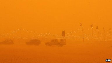Cars parked at desert camp in sandstorm
