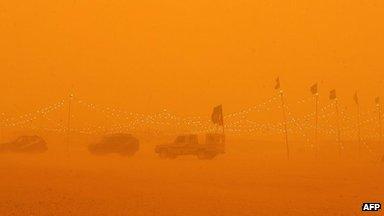 Cars parked at desert camp in sandstorm