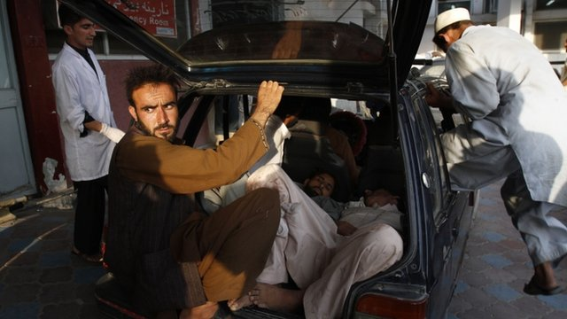 Injured Afghan men arrive by car to a hospital after a suicide attack