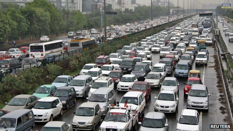 Heavy traffic moves along a busy road as it rains during a power-cut at the toll-gates at Gurgaon on the outskirts of New Delhi July 31, 2012