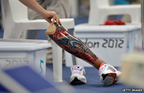 Swimmer's prosthetic leg is moved by official during swimming heat