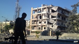 A photo purportedly showing a rebel fighter walks past a damaged building in Aleppo (2 September 2012)