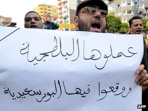 "An Egyptian man holds up a banner saying: ""Port Said fell in the trap of the baltajiya"" (3 February 2012)"