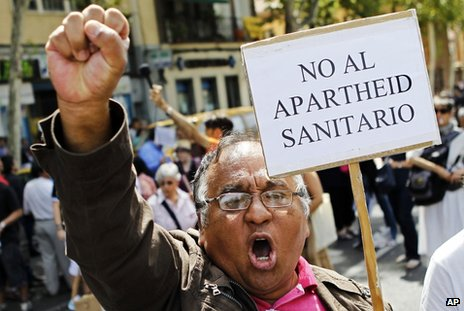 "An immigrant holds a banner reading ""No to the healthcare apartheid"" in Madrid, 1 September"