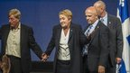 Pauline Marois on stage with security staff