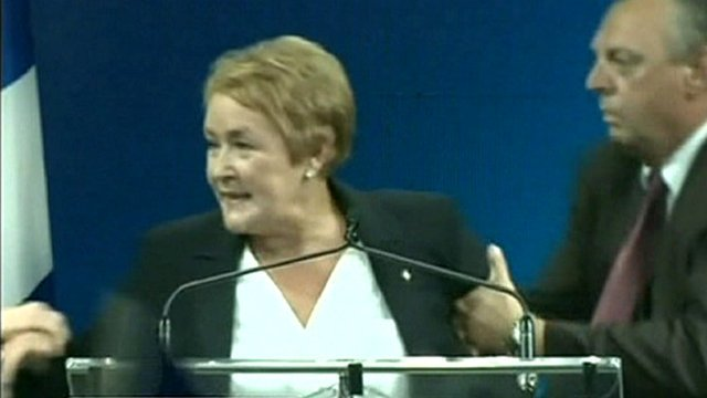Parti Quebecois leader Pauline Marois being dragged away from podium