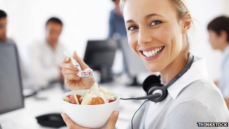 Woman eating food at her desk