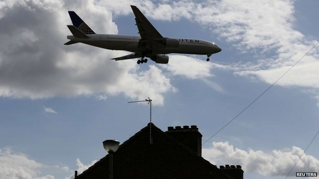 An airplane comes in over the top of houses to land at Heathrow Airport in west London