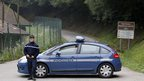 A gendarme blocks access to site where people were shot to death near Chevaline, French Alps,