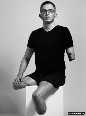 Giles Duley sitting on a plinth