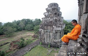 Monk sits on temple stairs