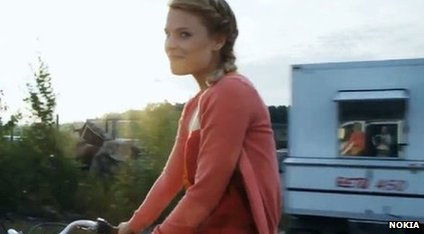A girl rides her bicycle. A reflection in a window shows that the video was recorded by a professional camera operator riding in a van.