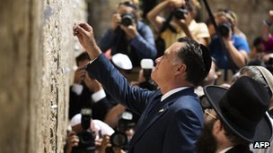 US Republican presidential candidate Mitt Romney places a message written on paper in the ancient stones of the Western Wall in Jerusalem's Old City