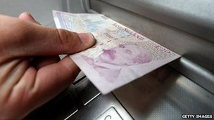 20 note being pulled from a cash machine