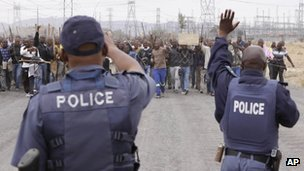 Police try to prevent striking mine workers marching to the Karee shaft at the Lonmin Platinum Mine near Rustenburg, South Africa Wednesday, Sept, 5, 2012