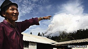 Man points at Tungurahua volcano