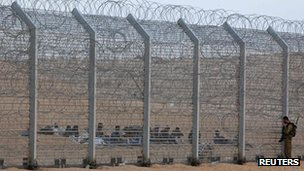 Soldier and a group of African migrants near the border fence between Israel and Egypt