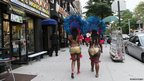 People in carnival costume walk in a street in New York city