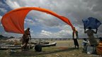 Hindu devotees hold up their clothes to dry in the wind