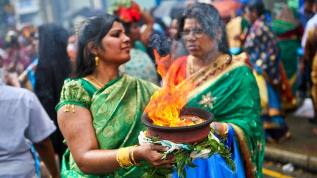 Hindu women hold bowls of steaming camphor at Ratha Yatra in London