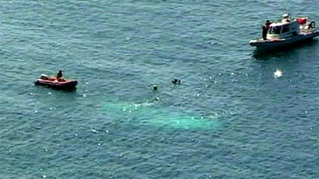 Sunken boat surrounded by rescue vessels