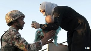 A Jordanian soldier helps a newly-arrived Syrian refugee with her baby after hundreds of people feeling the violence crossed the border from Syria into Jordan