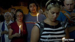 People participate in a candlelight vigil held for the victims of Tuesday night's Metropolis shooting in Montreal 5 September 2012