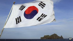 A South Korean flag flaps on a boat near islets called Dokdo in South Korea and Takeshima in Japan on 15 August, 2012
