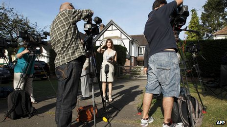 Journalists broadcast from outside a house believed to be the British home of a family shot dead in their car in the French Alps