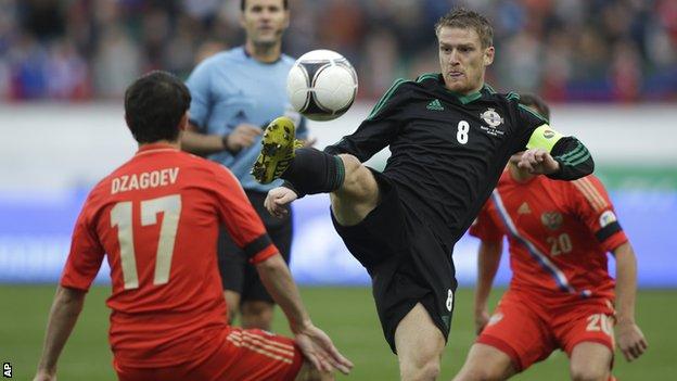Northern Ireland's Steven Davis gets to the ball before Alan Dzagoev of Russia