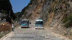 Two buses make their way across a road full of fallen rocks after a series of earthquakes near Zhaotong municipality at the border of southwest China's Yunnan and Guizhou province
