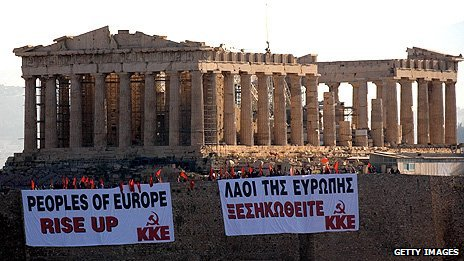 Members of the Communist Party of Greece (KKE) wave flags from the Acropolis Hill in Athens