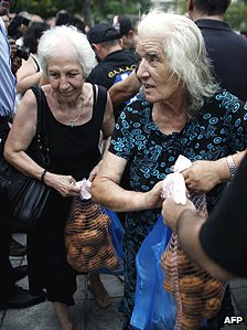 Two women receive free potatoes in Athens