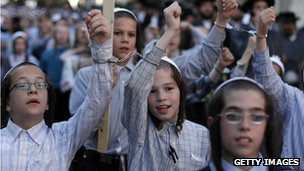 Ultra-Orthodox Jewish children wear handcuffs as they protest against conscription