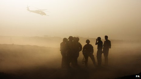 Soldiers in silhouette with helicopter overhead