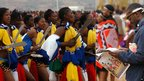L: Girls perform at the Reed Dance ceremony in Mbabane R: A man at the ceremony is distracted by his newspaper - Sunday 2 September 2012