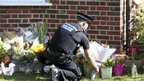 British police officers places flower tributes outside the home of Saad al-Hilli, in Claygate, Surrey
