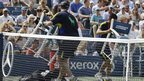 Ballboys return chairs and tennis gear to the sidelines after a gust of wind blew them onto the court during the US Open's first semi-final match between Andy Murray and Thomas Berdych in New York