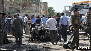 Iraqi security personnel inspect the site of a car bomb attack outside a French consular building in Nasiriya