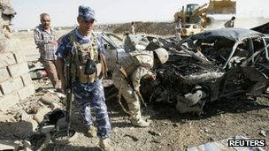 Security personnel inspect the site of a bomb attack in Kirkuk