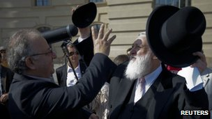 Rabbi Yitzhak Ehrenberg (R) gives his kippah to the head of the Turkish Community in Germany Kenan Kolat during a demonstration in Berlin against the controversial circumcision ruling