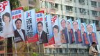 A man stands next to banners promoting candidates running the legislative elections, outside a public housing estate in Hong Kong 9/9/12