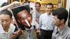 "A protester holds a defaced portrait of chief executive Leung Chun-ying with a ""Pinocchio's nose"" after Mr Leung, second right, voted at a polling station 9/9/12"