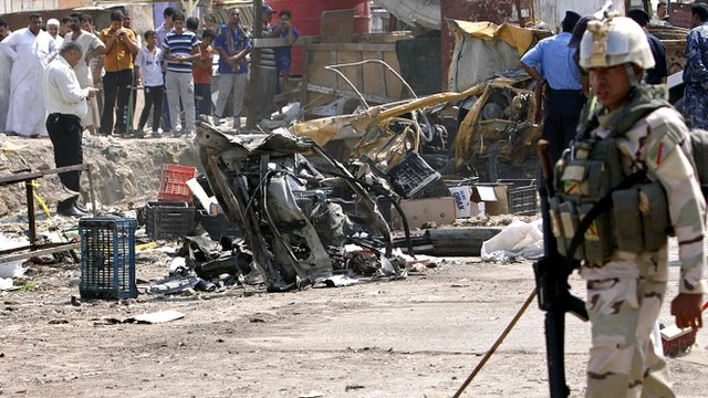 Security forces inspect the scene of a car bomb attack in Basra