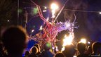 Festival-goers at Bestival, Isle of Wight, watching a mechanical dragon on stage