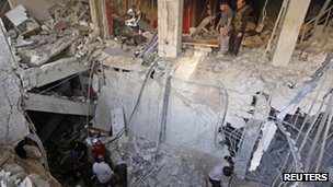 Members of the Free Syrian Army try to recover the body of their comrade from the rubble of a building destroyed by a jet strike in Aleppo on 9 September 2012