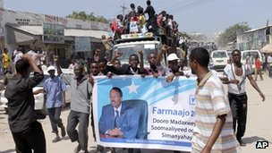 Somalis carry a banner with the photo of former Somali Prime Minister Mohamed Abdullahi during a mass rally in Mogadishu, Somalia, Thursday, 9 Aug